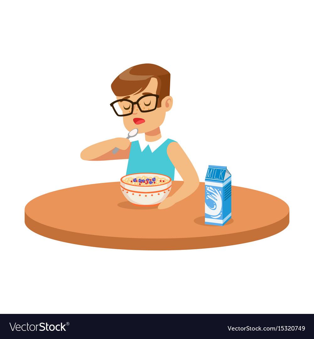 Cute boy eating porridge while having breakfast in