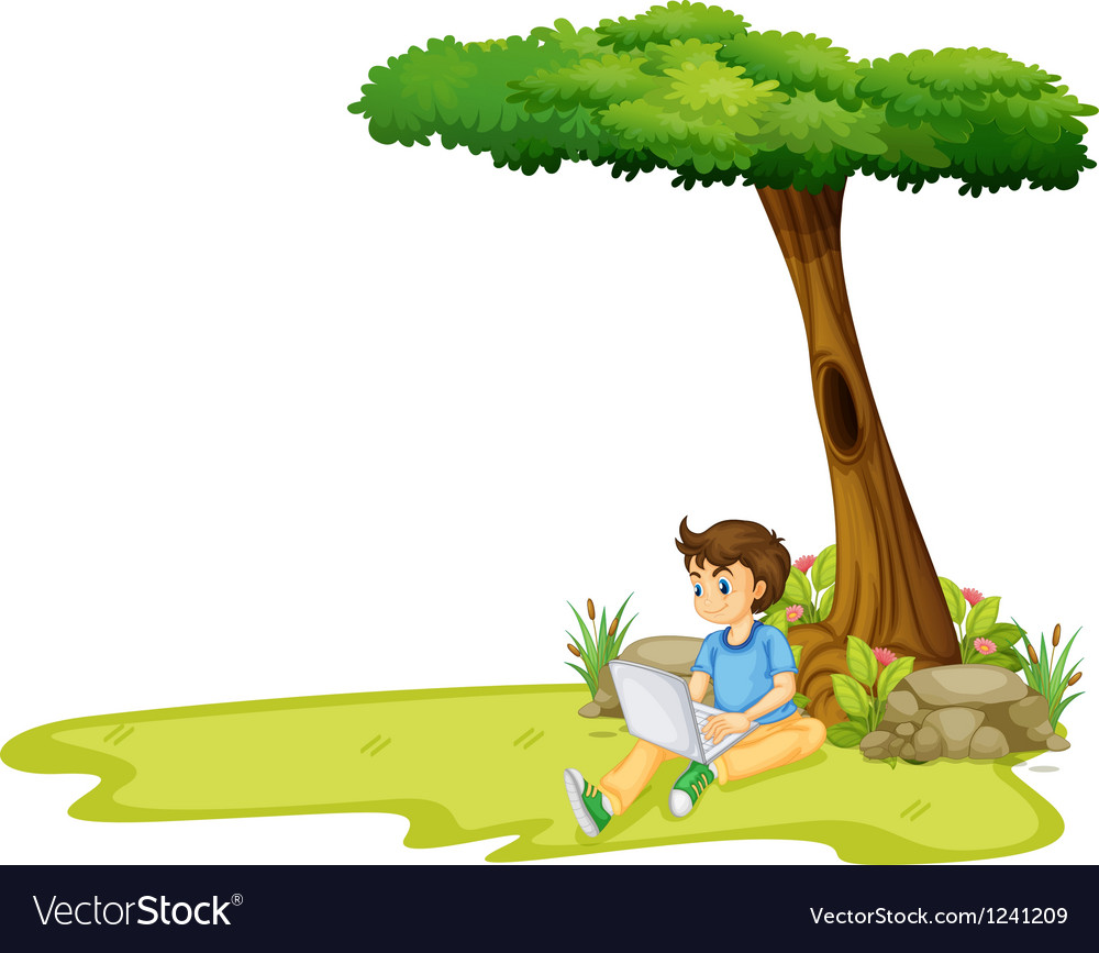 A boy using his laptop under a tree
