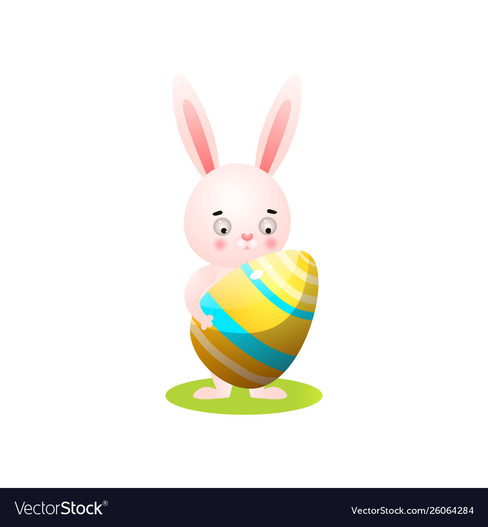 Cute easter rabbit on green grass with gold egg