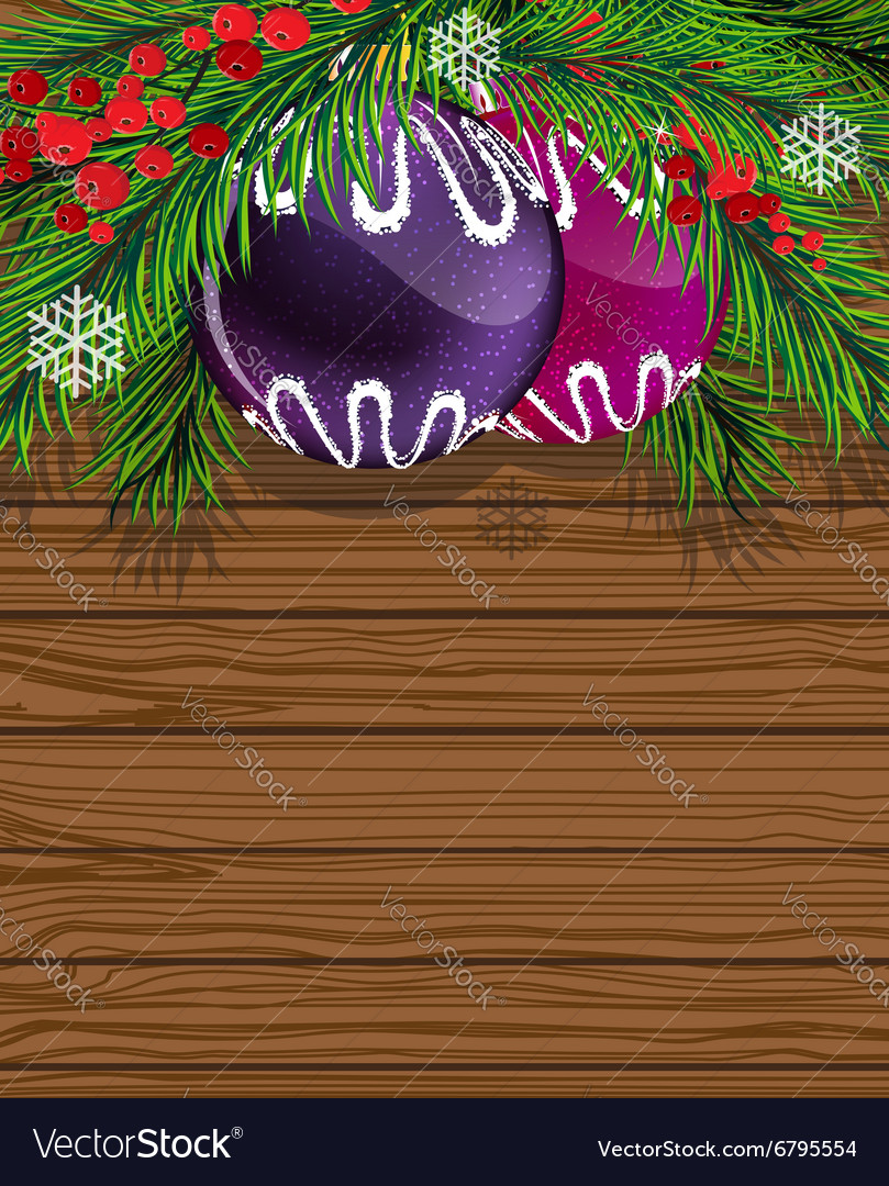 Baubles and fir branches on wooden board