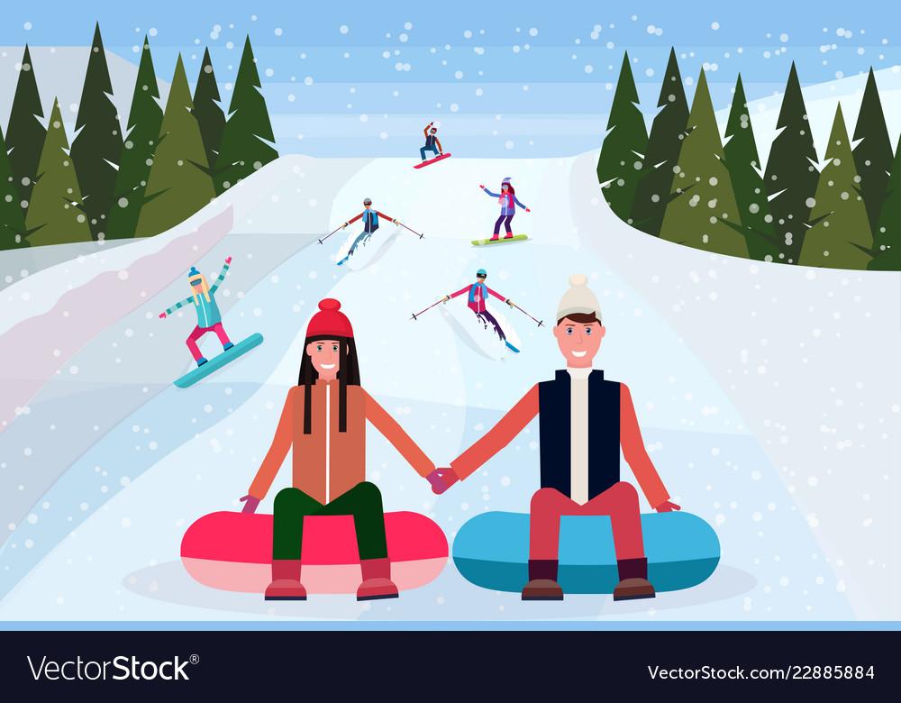 Couple sledding on snow rubber tube over