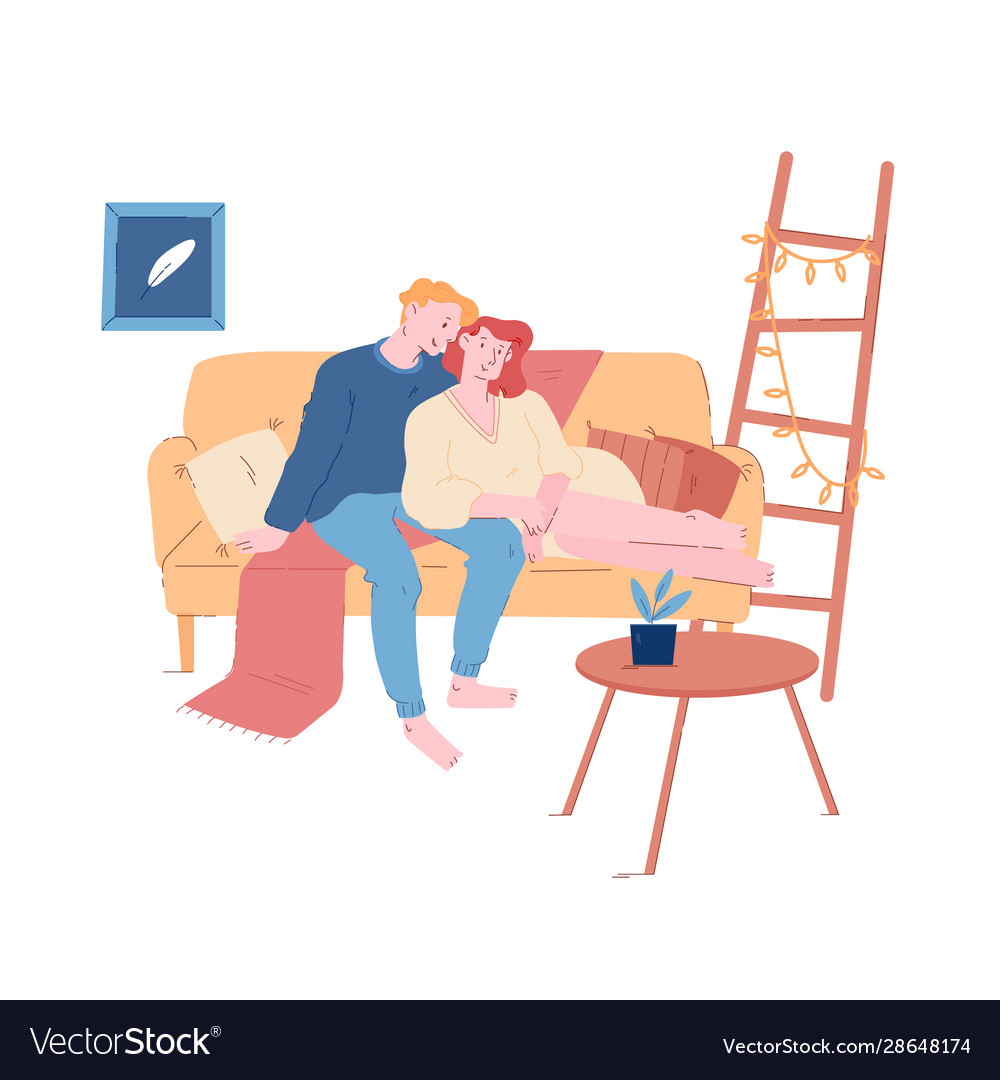 Young loving couple hugging sitting on couch at