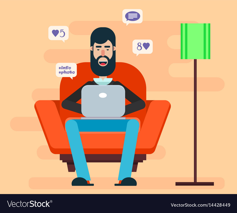 Bearded man sitting in a chair with a laptop on