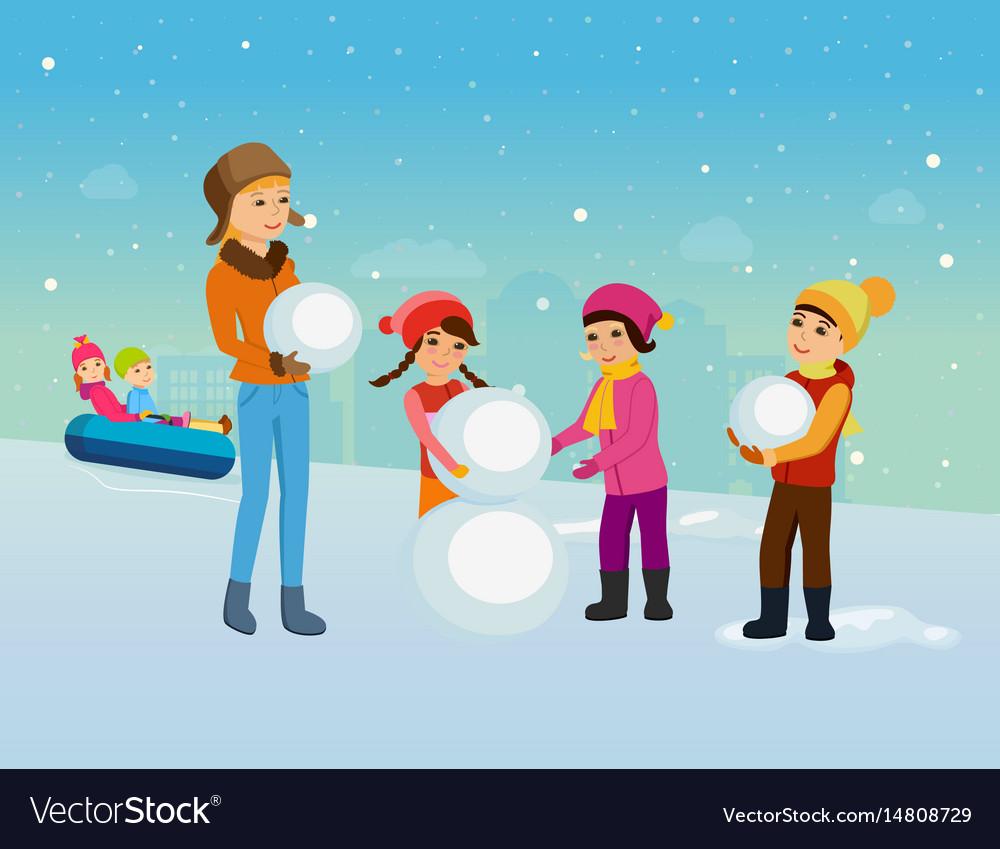 Children in winter clothes sculpt snowman
