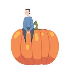 Little man sitting on top huge ripe pumpkin vector