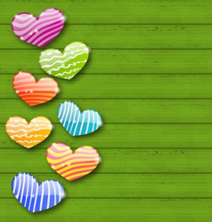 Multicolored striped hearts on green wooden vector image