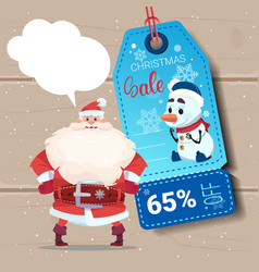 santa claus with christmas sale tag on wooden vector image