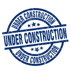 Under construction blue round grunge stamp vector