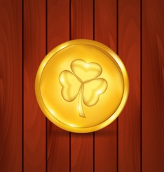 Golden coin with clover on brown wooden texture vector image