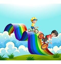 Kids riding bike over the rainbow vector image