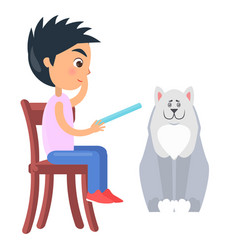 Boy on chair reads from tablet beside white dog vector