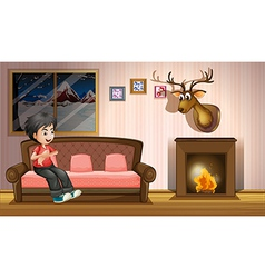 A boy sitting at the sofa near the fireplace vector image vector image