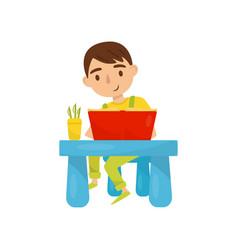 cute boy sitting at the table and reading a book vector image
