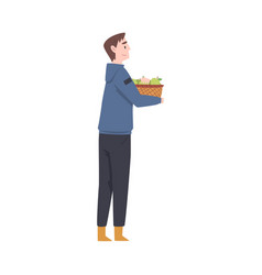 Young man carrying wicker basket full with vector
