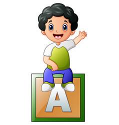 little boy sitting on alphabet cube vector image