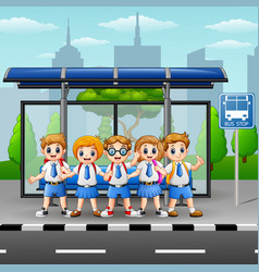 Happy school kids at the bus stop vector