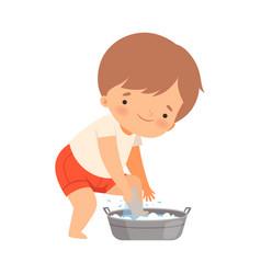 Little boy washing his legs in washbasin vector