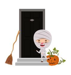 Boy with mummy costume and pumpkin in house door vector