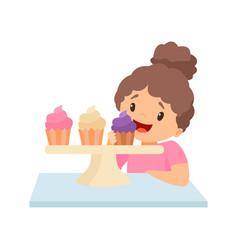 Cute happy little girl eating cupcakes vector