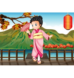 A girl in a kimono attire at the bridge vector