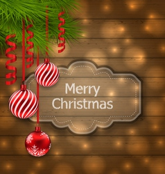 Christmas label with balls and fir twigs on wooden vector image