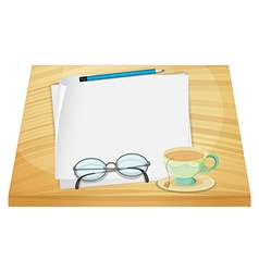 A wooden table with an empty paper and a cup of vector