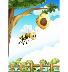 A tree near the fence with beehive and bee vector