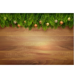 Christmas tree branches with baubles on a wooden vector image