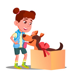Happy little girl takes out of gift box a dog vector