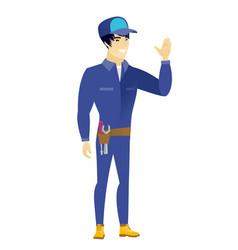 young asian mechanic waving his hand vector image