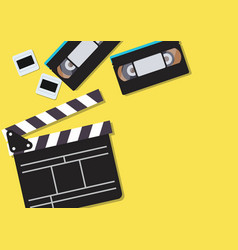 movie clapper and video cassette tapes on yellow vector image