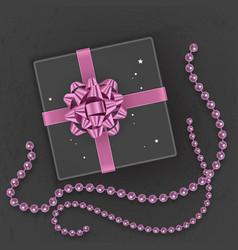 a realistic black gift box decorated with a pink vector image
