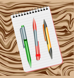 Notebook green pen red pen and yellow pen vector