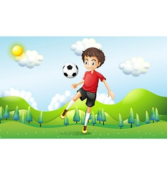 A boy practicing soccer at the hill vector image