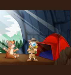 Safari boy and a brown bear in cave vector
