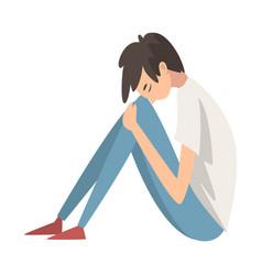 Depressed boy sitting on floor hugging his knees vector