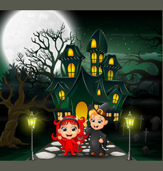 Happy halloween kids in front of the haunted house vector