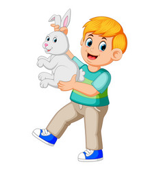 happy boy holding a rabbit vector image