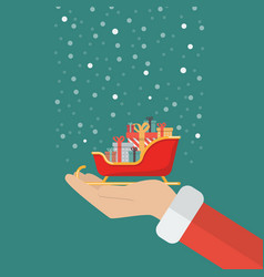 santa claus hand holding sleigh containing a full vector image vector image