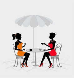 Two women sitting in street cafe vector