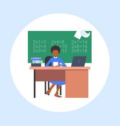 Female teacher sitting at desk in front vector