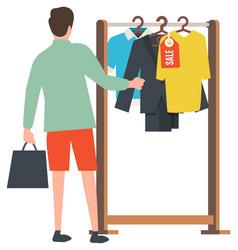 Man choosing stylish clothes at shipping center vector