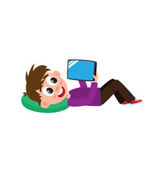Teenage boy lying on his back with tablet computer vector