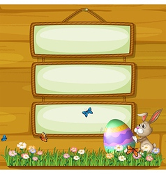A bunny pushing an egg in front of the hanging vector image
