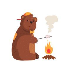 Cartoon bear frying marshmallow on fire in woods vector