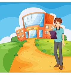 A boy holding a book standing outside the school vector