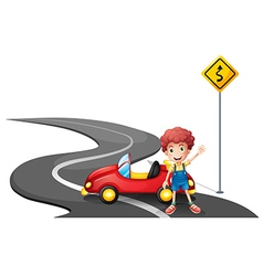 A young boy near a yellow signage with his car vector