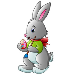 cartoon rabbit painting easter egg with a brush vector image