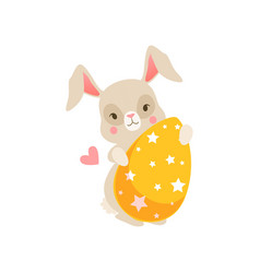cute cartoon bunny sitting holding yellow egg vector image
