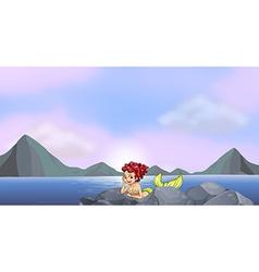A young mermaid near rocks at seaside vector
